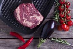 Ingrediënten voor het koken van gezond vleesdiner Ruw ongekookt rundvleeslapje vlees op de pan van de ijzergrill met groenten ove Royalty-vrije Stock Foto