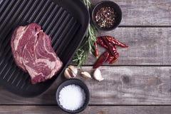 Ingrediënten voor het koken van gezond vleesdiner Ruw ongekookt rundvleeslapje vlees op de pan van de ijzergrill met zout en pepe Royalty-vrije Stock Afbeeldingen