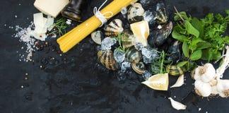 Ingrediënten voor het koken van spaghetti vongole Tweekleppige schelpdieren op afgebroken ijs, ruwe deegwaren, Parmezaanse kaaska Stock Foto