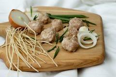 Ingrediënten voor het maken van soep met vleesballetjes ruwe vlees, uien en noedels op een houten raad royalty-vrije stock fotografie