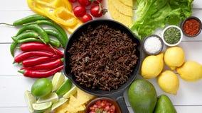 Ingredi?nten voor Chili con carne in het braden van ijzerpan op witte houten lijst stock videobeelden