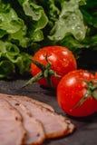 Ingredi?nten voor het koken Italiaanse bruschetta op donkere lijst Italiaanse bruschetta met kersentomaten, kaassaus, saladeblade stock afbeeldingen