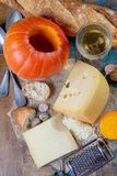 Ingrediens para el plato suizo estacional tradicional, la 'fondue' de la calabaza con quesos del gruyer y del emmental, el vino b fotografía de archivo