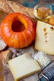 Ingrediens para el plato suizo estacional tradicional, la 'fondue' de la calabaza con quesos del gruyer y del emmental, el vino b foto de archivo libre de regalías