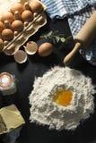 Ingredienser av framställning av en kaka eller av en paj, med ägg, socker och smör royaltyfri bild