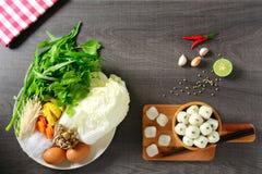 Ingredienser av thai mat, limefrukt, chili, vitlök och olika grönsaker, två ägg på den vita maträtten och fiskbollar i träbunken, arkivbild