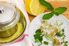 Ingredienser för örtte, citron och fragment av den glass tekannan royaltyfri foto