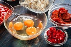 Ingredienser för att förbereda frittata - ägg, korvchorizo, röd peppar, paprika, tomater, chili och ost på trätabellen Arkivbild