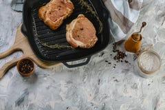 Ingredienser för att laga mat den sunda köttmatställen Rå okokta nötköttbiffar med kryddor, träbakgrund, gjutjärn som grillar pan royaltyfria foton