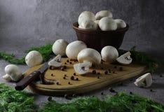 Ingredienser för att laga mat läcker mat champignonchampinjoner och ny grön dill Svartpepparärtor spridda på tabellen arkivbild