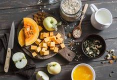 Ingredienser för att laga mat muttern mjölkar havremjölet med pumpa, äpplen och honung på träbrun bakgrund Royaltyfri Bild