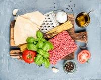 Ingredienser för att laga mat pasta Bolognese Spagetti parmesanost, tomater, metallrivjärn, olivolja, vitlök som finhackas Arkivfoto