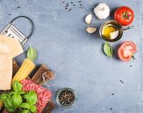 Ingredienser för att laga mat pasta Bolognese Spagetti parmesanost, tomater, metallrivjärn, olivolja, vitlök som finhackas Arkivfoton