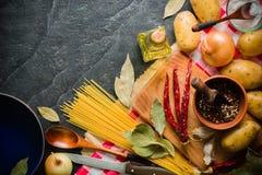 Ingredienser för att laga mat: potatisar som är salta, peppar, lök, vitlök på en mörk stentabell Royaltyfri Fotografi