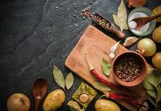 Ingredienser för att laga mat: potatisar som är salta, peppar, lök, vitlök på en mörk stentabell Royaltyfria Bilder