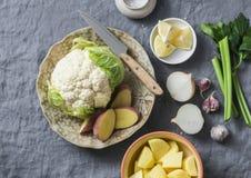 Ingredienser för att laga mat puré för potatisblomkålsoppa på en grå bakgrund, bästa sikt sund vegetarian för mat fotografering för bildbyråer