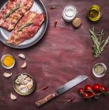 Ingredienser för att laga mat rå lammstöd i en panna med örter, en kniv, smaktillsats, tomatställe för text, ram på trälantlig ba Royaltyfri Fotografi