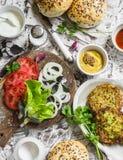 Ingredienser för att laga mat vegetariska hamburgare - zucchinihamburgare, hemlagade bullar, tomater, lökar, örter, kryddor och s fotografering för bildbyråer