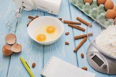 Ingredienser för degen Mjöl, ägg och den tomma anteckningsboken på svart skrapade bakgrund Royaltyfri Bild