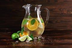 Ingredienser för en citrus lemonad på en träbakgrund Limefrukt apelsiner, mintkaramell bredvid en krus av fruktfruktsaft Kafédrin Royaltyfri Bild