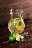 Ingredienser för en citrus lemonad på en träbakgrund Limefrukt apelsiner, mintkaramell bredvid en krus av fruktfruktsaft Kafédrin Fotografering för Bildbyråer