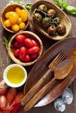 Ingredienser för en sallad Träoval platta Träsked och gaffel arkivfoton