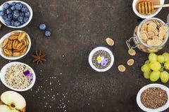 Ingredienser för en sund säsongsbetonad höstfrukost: äpplen druvor, pecannöt, chiafrö, quinoa, linfrö, honung arkivbilder