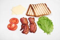 Ingredienser för framställning av smörgåsen nya grönsaker, tomater, bröd, becon Isolerat på vit bakgrund, bästa sikt, kopia royaltyfri foto