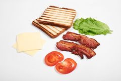 Ingredienser för framställning av smörgåsen nya grönsaker, tomater, bröd, becon Isolerat på vit bakgrund, bästa sikt, kopia royaltyfri fotografi