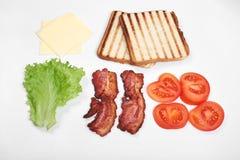 Ingredienser för framställning av smörgåsen nya grönsaker, tomater, bröd, becon Isolerat på vit bakgrund, bästa sikt, kopia royaltyfria bilder