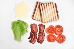 Ingredienser för framställning av smörgåsen nya grönsaker, tomater, bröd, becon, ost Isolerat på vit bakgrund, överkant fotografering för bildbyråer