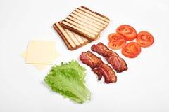 Ingredienser för framställning av smörgåsen nya grönsaker, tomater, bröd, becon, ost Isolerat på vit bakgrund, överkant arkivfoton
