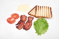 Ingredienser för framställning av smörgåsen nya grönsaker, tomater, bröd, becon, ost Isolerat på vit bakgrund, överkant royaltyfri fotografi