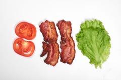 Ingredienser för framställning av smörgåsen nya grönsaker, tomater, bröd, becon, ost Isolerat på vit bakgrund, överkant royaltyfria bilder