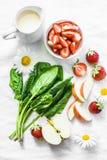 Ingredienser för framställning kokosnöt av den probiotic yoghurten, spenat, äpple, jordgubbedetoxsmoothie på en ljus bakgrund, bä arkivfoto