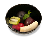 Ingredienser för fruktsalladen i den isolerade svarta keramiska bunken Royaltyfri Foto