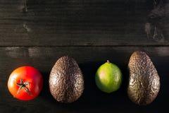 Ingredienser för guacamole, avokado, limefrukt, tomat, på mörkt trä Arkivfoton