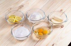 Ingredienser för hem- kaka i glass bunkar Arkivfoto