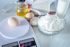 Ingredienser för matlagning Mjöl och socker i en exponeringsglasbehållare, ägg och smör på en vit tabell royaltyfri fotografi