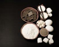 Ingredienser för söt bakelse på en svart träbakgrund tonat Fotografering för Bildbyråer