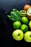 Ingredienser för smoothie Gräsplan bär frukt på svart träbakgrund Apple limefrukt, spenat, kiwi detox sund mat Top beskådar kopia Royaltyfri Foto