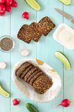 Ingredienser för strikt vegetariansmörgås med gräddost, nytt gurka-, rädisa- och chiafrö på mintkaramellträbakgrund royaltyfri fotografi