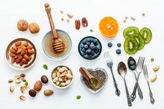 Ingredienser för sunda foods bakgrund, muttrar, honung, bär Royaltyfri Fotografi