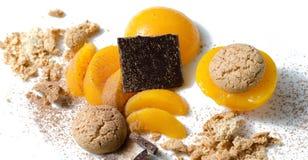 Ingredienser för traditionell italiensk efterrätt: persikor amaretti, choklad Arkivfoto