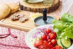 Ingredienser för att laga mat hamburgare Rå jordnötköttköttkotletter på träskärbrädan, röd lök, körsbärsröda tomater, gräsplaner, Royaltyfri Fotografi