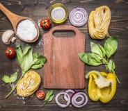 Ingredienser för att laga mat vegetarisk pasta med mjöl, grönsaker, olja och örter, lök, peppar som ut läggas runt om skärbräda p Arkivfoto