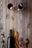 ingredienser mulled wine Vin i flaska, kryddakanel och badian, citrusfrukter på mörk träbakgrundsöverkant Royaltyfri Fotografi