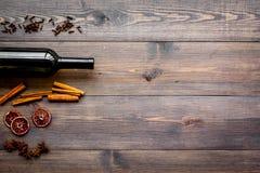 ingredienser mulled wine Vin i flaska, kryddakanel och badian, citrusfrukter på mörk träbakgrundsöverkant Royaltyfria Foton