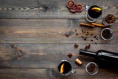 ingredienser mulled wine Vin i flaska, kryddakanel och badian, citrusfrukter på mörk träbakgrundsöverkant Arkivfoto
