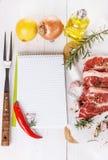 Ingredienser och kök bearbetar på vitbakgrund Receptbok och ingredienser för att laga mat kött Royaltyfri Foto
